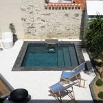 Petite piscine sophistiquée avec un liner gris foncé et des margelles en ardoise située sur la cote atlantique du côté de Nantes.